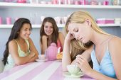 image of saddening  - Young woman with a hangover sitting at a table with two friends - JPG