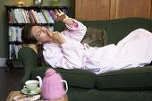 Woman Enjoying Eating Chocolate On Sofa