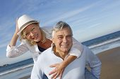 image of piggyback ride  - Portrait of cheerful senior couple having fun at the beach - JPG