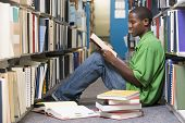 stock photo of reading book  - Man sitting on floor in library reading book - JPG