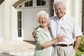 image of old couple  - Senior couple standing outside their home - JPG