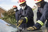 image of crew cut  - Two firefighters cutting out a windshield after an accident with another firefighter in background - JPG