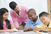 stock photo of pre-adolescent child  - Students in class reading with teacher helping  - JPG
