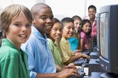 stock photo of pre-adolescent child  - Six children at computer terminals with teacher in background  - JPG