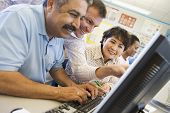 stock photo of middle class  - Teacher helping adult students at computer terminals - JPG