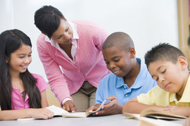 foto of student teacher  - Students in class reading with teacher helping  - JPG