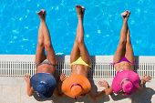 stock photo of sunbathing woman  - Three women in bikini wearing a straw hat by the swimming pool - JPG