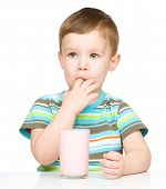 stock photo of finger-licking  - Cute little boy with a glass of milk licking his finger - JPG