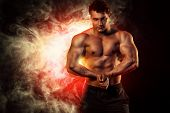 stock photo of abdominal muscle  - Portrait of a handsome muscular bodybuilder posing over dark background - JPG