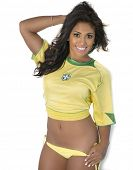 Beautiful smiling happy woman dressed in soccer top with Brazil flag and bikini bottom.