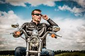foto of biker  - Biker man wearing a leather jacket and sunglasses sitting on his motorcycle looking at the sunset - JPG