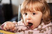 stock photo of love bite  - Portrait of a cute little baby girl eating pasta for dinner - JPG