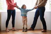 stock photo of scared  - Two Parents Fighting Over Child In Divorce Concept - JPG
