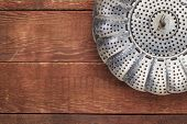 metal steamer basket on red rustic barn wood table with a copy space