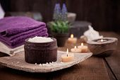 stock photo of purity  - Spa and wellness setting with natural bath salt candles towels and flower. Wooden dayspa nature set