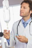 foto of intravenous  - Professional doctor examining intravenous drip in hospital - JPG