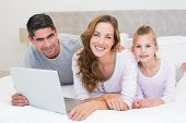 Portrait of smiling family with laptop in bed