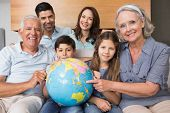 picture of extend  - Portrait of an extended family sitting on sofa with globe in the living room at home - JPG