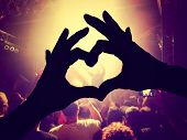 picture of singer  - a crowd of people at a concert  with a heart silhouette on the singer - JPG