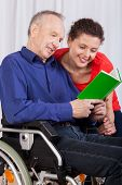 image of disable  - A disabled man and a nurse reading a book together - JPG