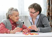 foto of geriatric  - Elder care nurse playing jigsaw puzzle with senior woman in nursing home - JPG