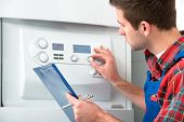 stock photo of gas-pipes  - Technician servicing the gas boiler for hot water and heating