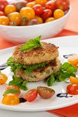 picture of cooked crab  - Close up of crab cakes and cherry tomato salad appetizer garnished with basil and balsamic vinegar sauce - JPG