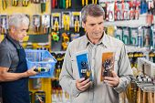 pic of hardware  - Male customer choosing soldering iron with worker working in background at hardware store - JPG