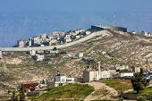 image of west village  - Small village and palestinian town on the hill behind separation wall on the West Bank in Israel - JPG