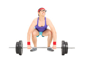 foto of struggle  - Nerdy guy struggling to lift a barbell isolated on white background - JPG