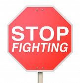 stock photo of stop fighting  - Stop Fighting words on a red road or traffic sign telling you to negotiate with your enemy to reach a truce or ceasefire and end the violence - JPG