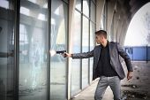 foto of gun shop  - Well dressed handsome young detective or policeman or mobster standing in an urban environment aiming and firing a gun to a window glass with a determined expression - JPG