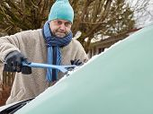 picture of ice-scraper  - The mid adult man cleans a frozen windshield - JPG