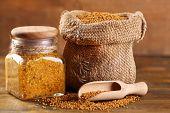 foto of mustard seeds  - Mustard seeds in bag and Dijon mustard in glass jar on wooden background - JPG