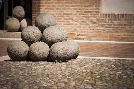 stock photo of cannon-ball  - Cannon balls inside a medieval castle in Italy - JPG