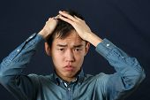 stock photo of disappointed  - Disappointed young Asian man making face and looking at camera - JPG