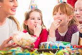 stock photo of party hats  - Children on birthday party nibbling candies wearing party hats - JPG