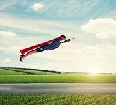 picture of cloak  - serious businesswoman dressed as a superhero in red mask and cloak flying at outdoor over beautiful landscape background - JPG