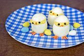 foto of easter candy  - Deviled eggs created like Easter chicks with candy eggs on blue and white checkered plate on wood - JPG