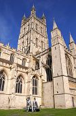 stock photo of nun  - Cathedral church of St Peter and the Holy and Indivisible Trinity with metal nun statues in the foreground Gloucester Gloucestershire England UK Western Europe - JPG