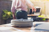 image of braai  - Stack of plates on a table outside in a garden with a man attending to a barbecue in the background - JPG