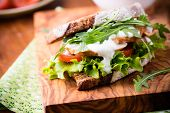 stock photo of tomato sandwich  - Rye toast sandwich with green leaf tomato and chicken selective focus - JPG