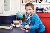 stock photo of retort  - The happy boy with microscope at home - JPG