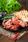 picture of bacon strips  - Fried bacon and toast on a black plate on a wooden background - JPG