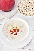 pic of porridge  - Oat porridge with red apple slices on white wooden table top view - JPG