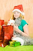 stock photo of tawdry  - new year girl with two pet rabbits sitting in home - JPG