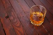 picture of tumbler  - Tumbler glass full of whisky standing on a wooden table - JPG