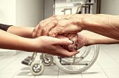 foto of wheelchair  - Hands of an elderly man holding the hand of a younger woman on wheelchair background - JPG