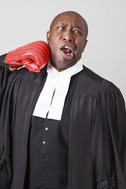 stock photo of toga  - bald black man wearing canadian lawyer toga getting punch in the face by a red boxing glove - JPG