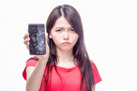 pic of frown  - Frowning Chinese woman OOF holding cell phone with cracked screen - JPG